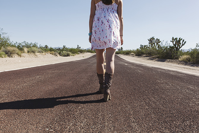 A woman walks down the middle of a highway in the desert.